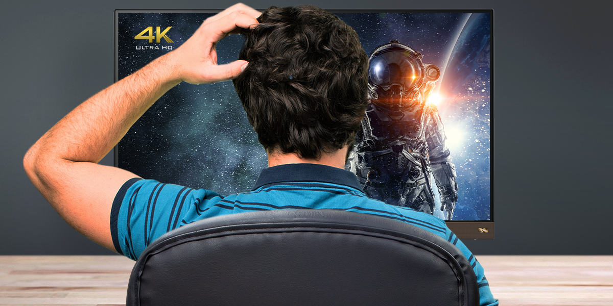 A confused man scratching his head in front of a 4K UHD monitor.