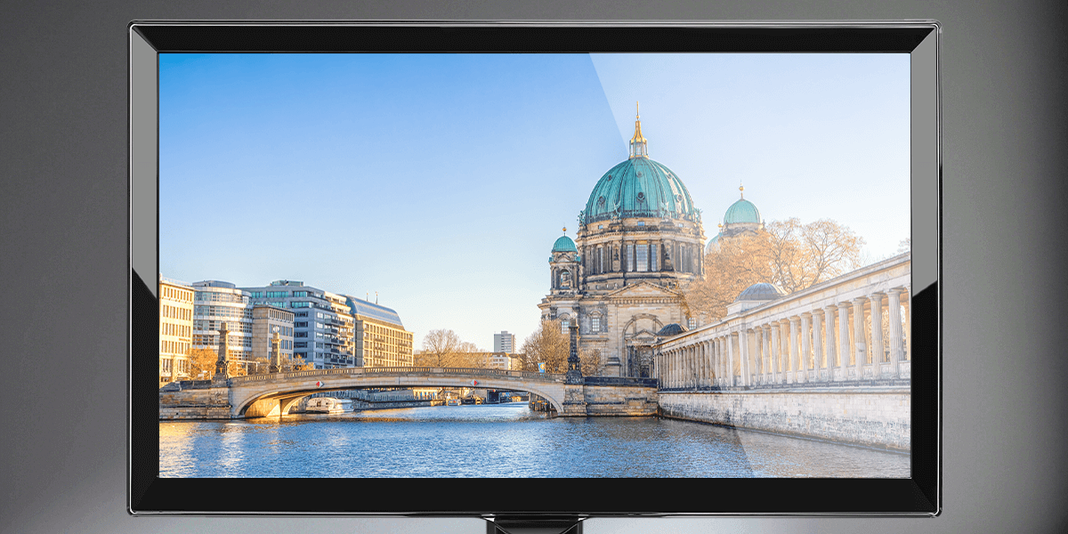 glossy monitor screen shows a cathedral by a river