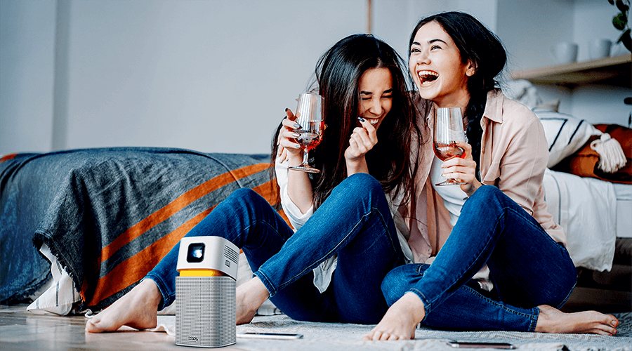 two girls watching big screen entertainment on a mini portable projector in a smaller room